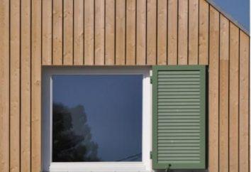 Instalação de janelas em uma casa de madeira com as mãos